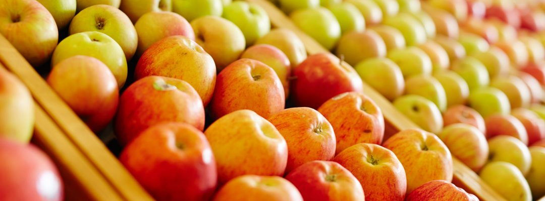 Variety of apples of different sorts in modern hypermarket